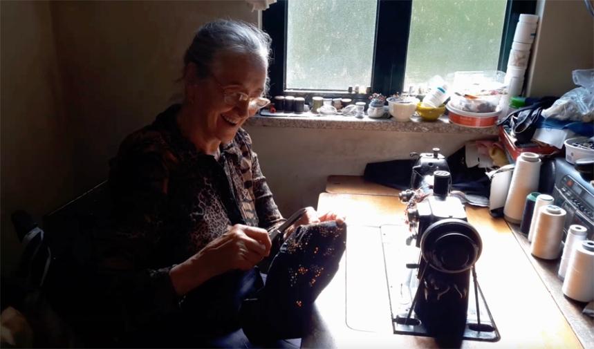 Dona Celeste a trabalhar na máquina de costura
