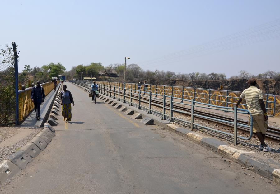 Pessoas a atravessar a fronteira e outros à espera de turistas