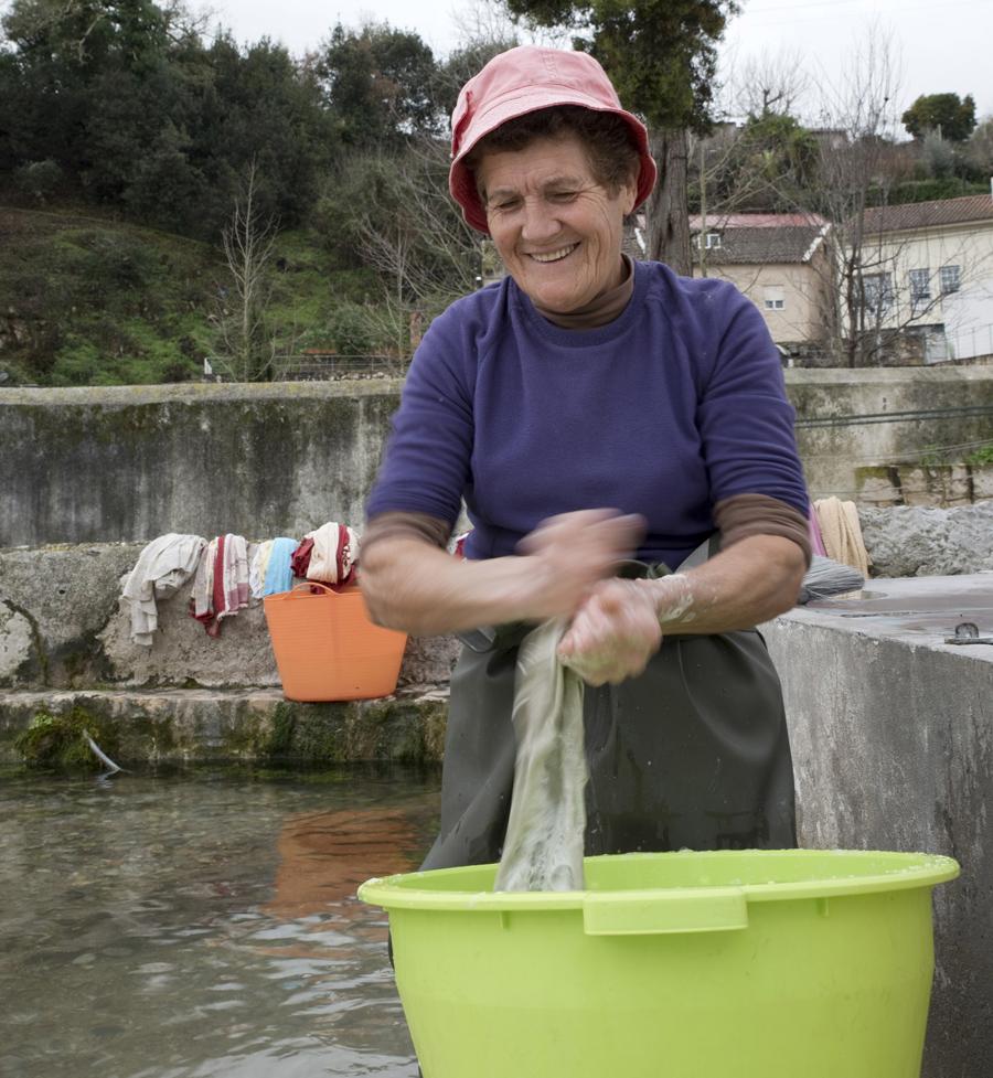 Uma mulher lava roupa no tanque