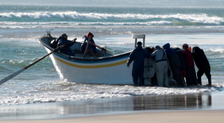 Barco a ser empurrado até quebrar a onde. Para deslizar facilmente a embarcação é rasa em baixo